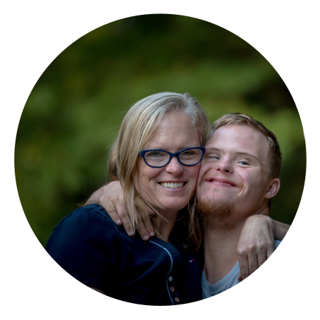 a young man with Down Syndrome and his mother embrace. they are smiling.