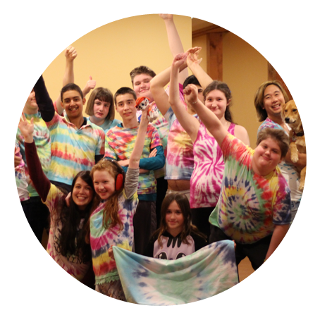 a group of young people smile at the camera. they are dressed in tie dye t-shirts.