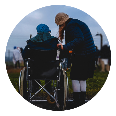 a young woman accompanies an older individual in a wheelchair. they are outside, with their backs to the camera.